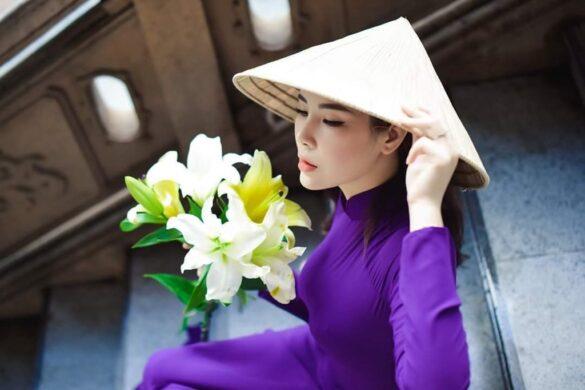 Nữ sinh mặc áo dài tím đẹp bên hoa loa kèn